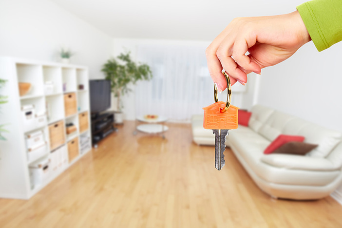 Hand with house key in foreground, living room with light wood floors, white couch and white shelves in background