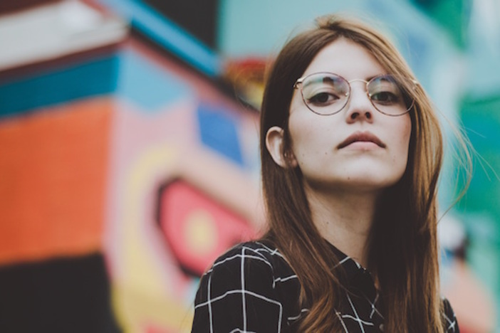 woman in plaid shirt with glasses standing in front of colorfully painted building