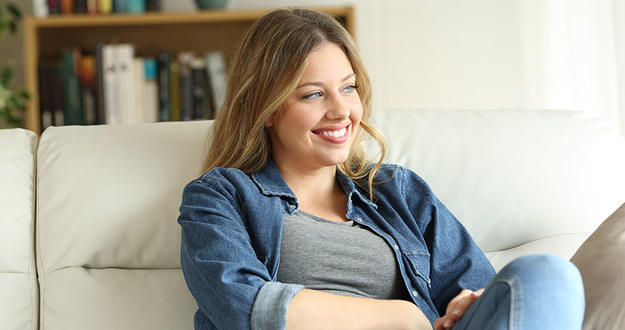 Relaxed happy woman looking at side sitting on a couch in the living room at home