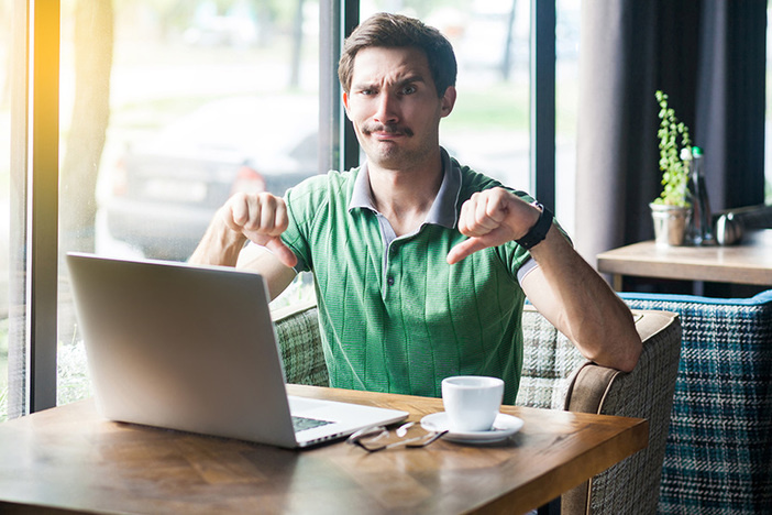 Dislike! Young dissatisfied businessman in green t-shirt sitting, working on laptop, looking at camera and showing thumbs down. business and freelancing concept. indoor shot near big window at daytime