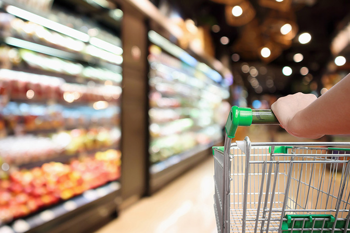 woman hand hold supermarket shopping cart with abstract blur organic fresh fruits and vegetable on shelves in grocery store unfocused background