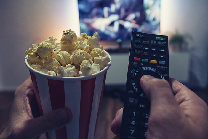 young man Watching a Movie in his living room with popcorn and remote