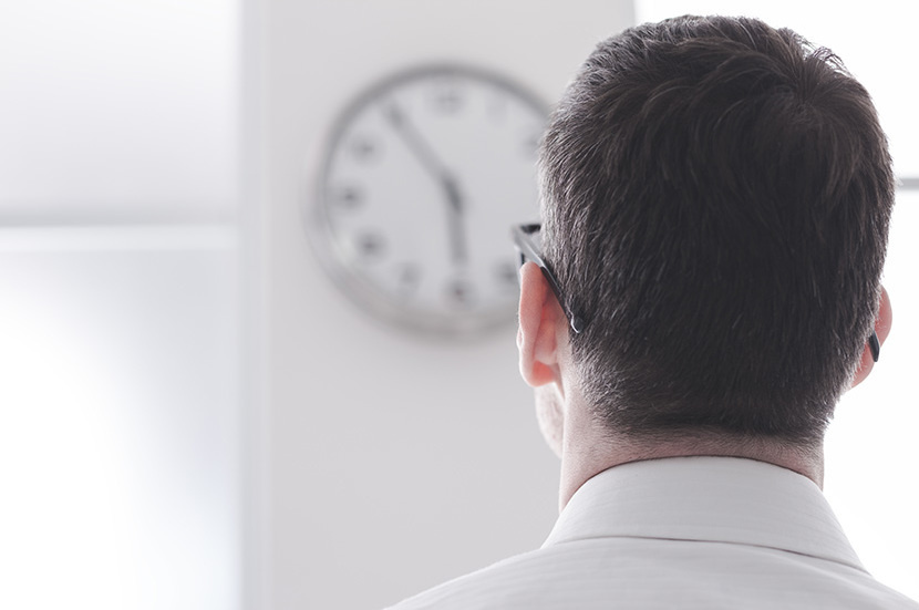 Businessman in the office staring at the clock, back view, time slave and stress concept