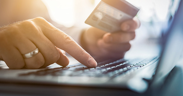 Hands holding credit card and using laptop. Online payment and shopping concepts.