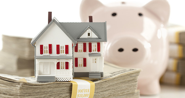 Small House and Piggy Bank with Stacks of Hundred Dollar Bills Isolated on a White Background