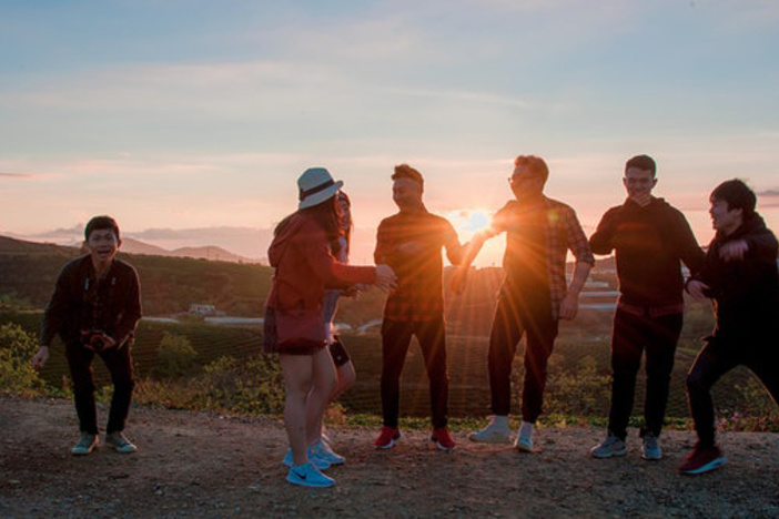 group of young adults outside looking at a sunset