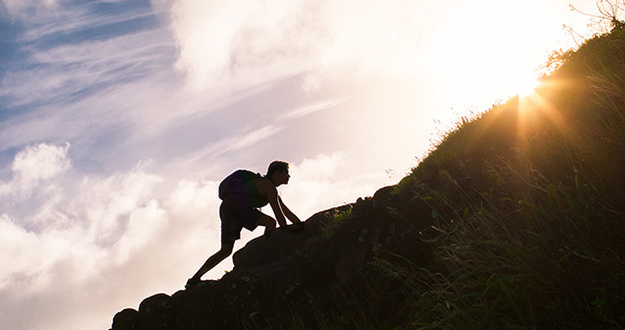 silhouette of man wearing backpack climbing uphill in sunshine