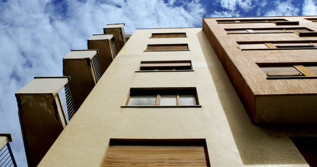 looking up at a multilevel apartment building from the ground blue sky with clouds in backdrop