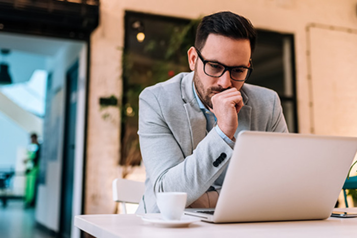Pensive young entrepreneur looking at laptop screen and drinking coffee at table in cafe