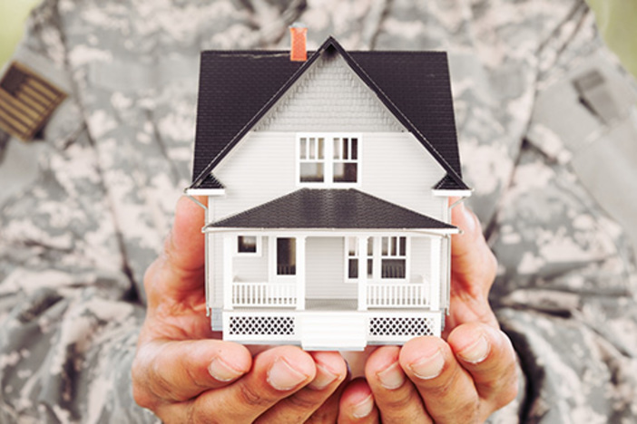 military service member holding model home in hands