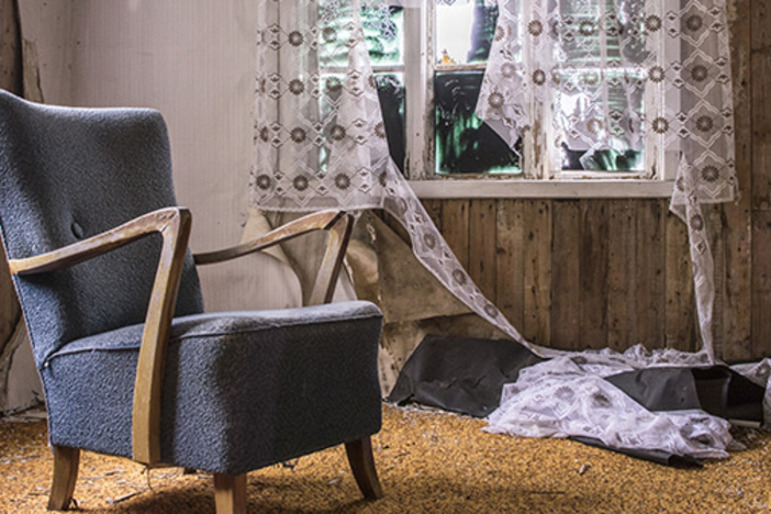 disheveled living room with broken window fluttering curtains blue apholstered chair