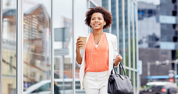 young smiling african american businesswoman with coffee cup in city