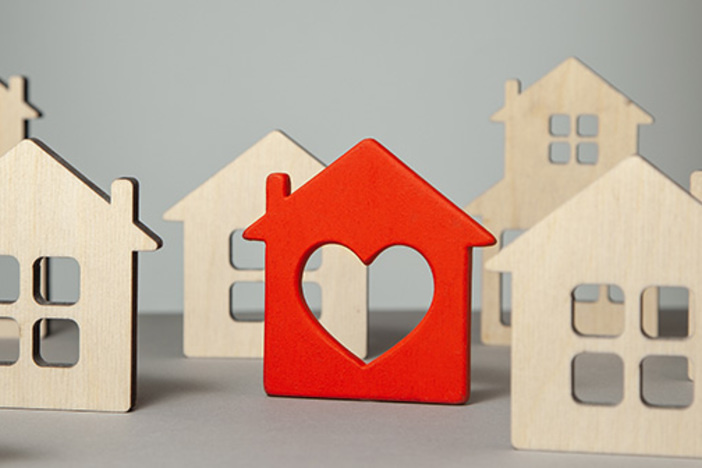 natural color wooden house cutouts with one painted red with a heart cutout added