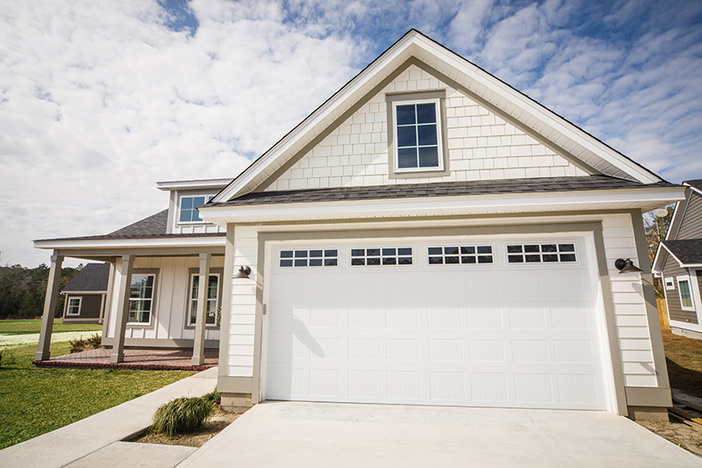 home with white siding and two-car garage with room above