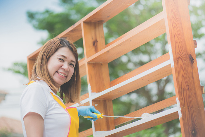 Asian girl paiting wooden shelf by roller outdoors