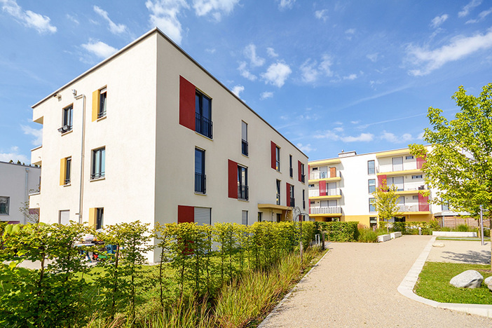 white apartment building with colorful window trim blue sky in background manicured grass and walkway