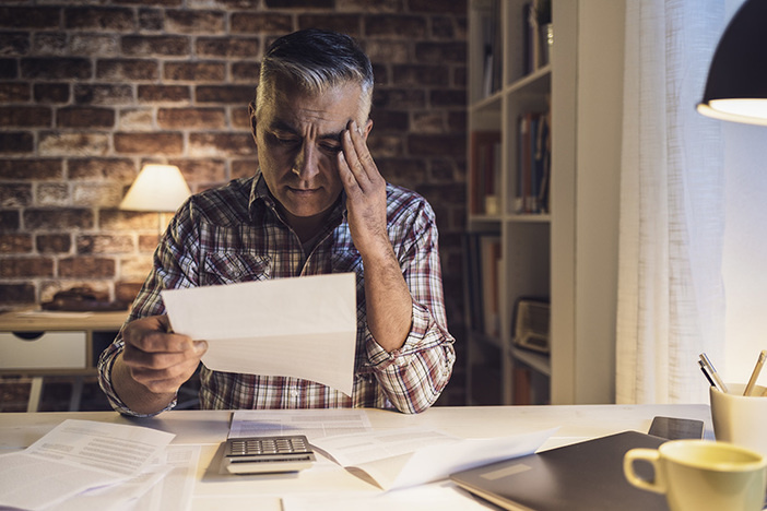 Worried mature man checking his domestic bills at home, he is concerned and reading his financial statements