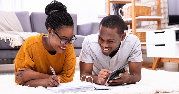 Young African Couple Lying On Carpet Invoice With Calculator