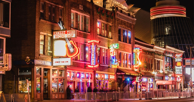 downtown Nashville, Tennessee at night bars lit up with neon signs