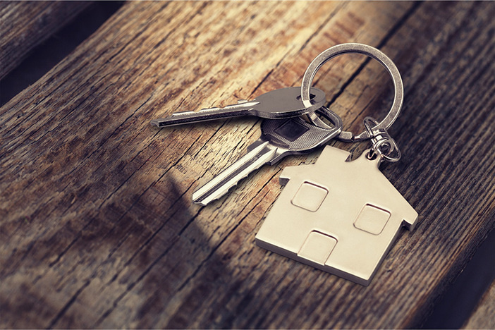 keys on a keychain shaped like a house laying on a piece of wood