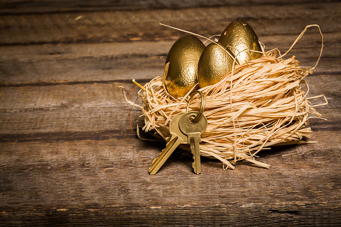 bird's nest on a wooden plank surface with three golden eggs in next and two keys on a key ring hanging from nest