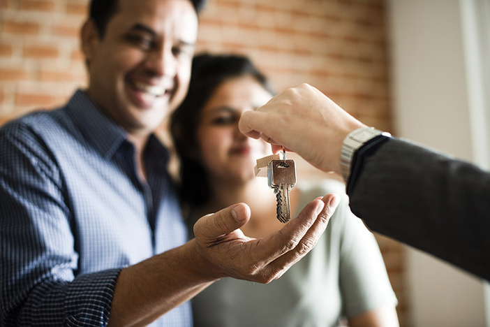 Cheerful couple receiving keys to their new home