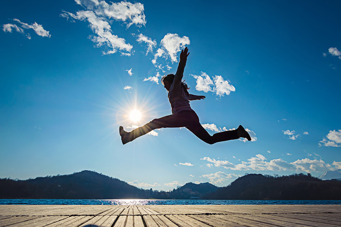 silhouette of girl jumping in the sun