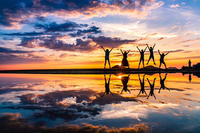 young people silhouettes jumping with sunset in background and water in foreground reflections of silhouettes clearly visible in water