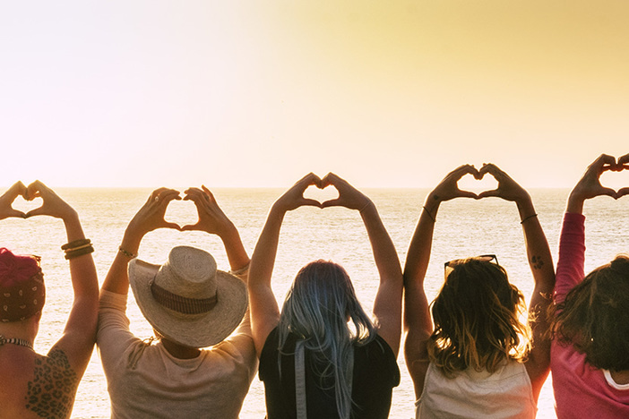 Group of diverse young women enjoying the sunset at the sea doing hearth symbol with hands