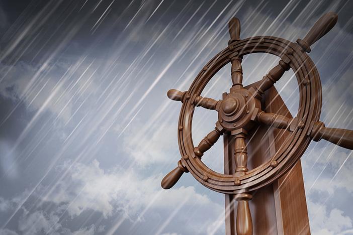 wheel of ship against a dark cloudy sky while raining