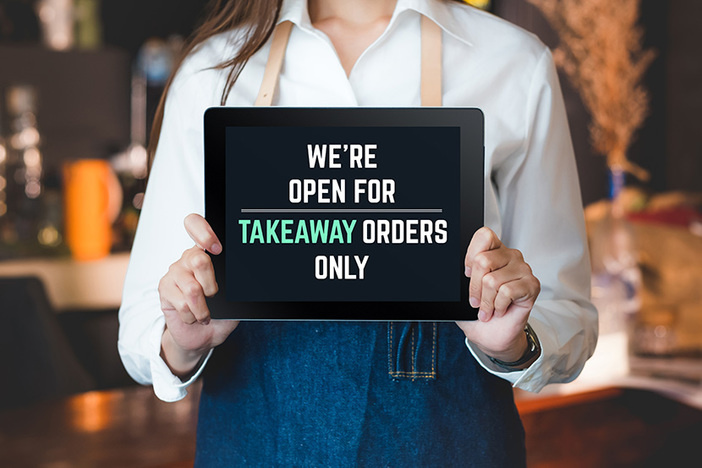 asian barista holding tablet sign we're open for takeaway orders only infront of counterbar.social distancing concept when coronavirus is outbreak in city