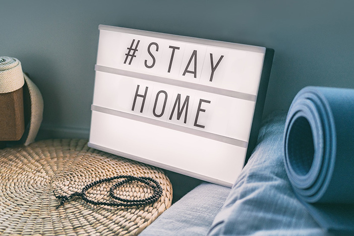 Coronavirus Yoga at home sign lightbox with text hashtag #STAYHOME glowing in light with exercise mat, cork blocks, strap meditation pillows. COVID-19 banner to promote self isolation staying at home.
