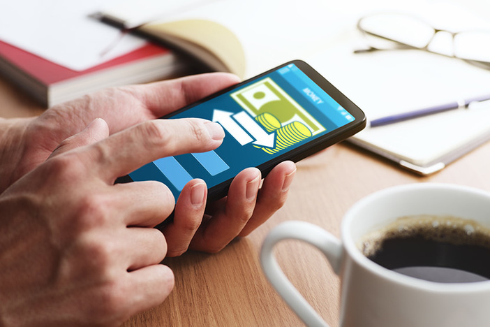 Using smartphone for money transfer and banking. Closeup of male touching smartphone screen for using app at table.