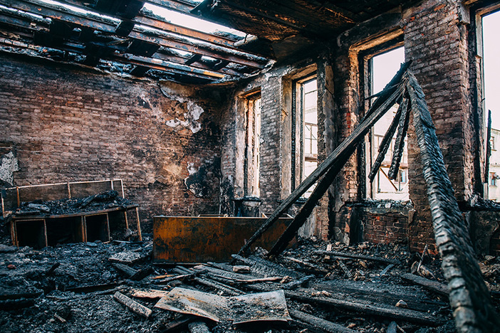 Burnt room interior with walls, furniture and floor in ash and coal, ruined building after fire, toned