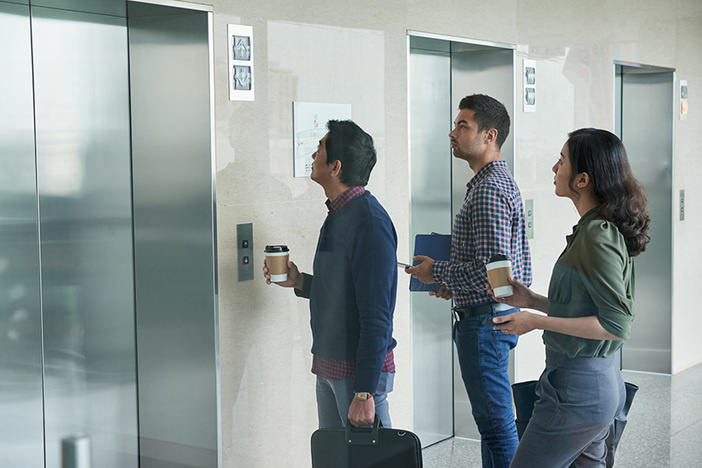 Business people waiting for elevator in office hall