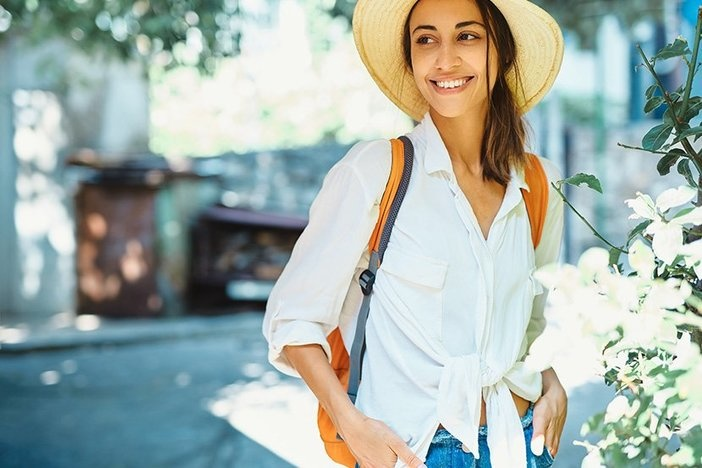 portrait happy carefree woman tourist in straw hat, white shirt walking and exploring small streets. Vacation in Thailand. Tourism and travel concept.