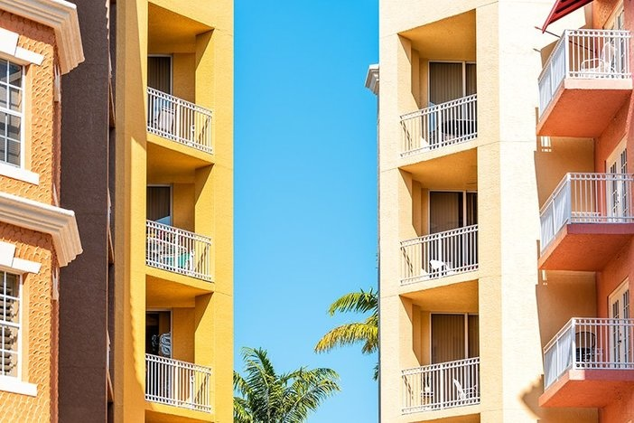Colorful condos, condominiums colorful, orange yellow multicolored buildings facade exterior with windows, palm trees, mansion real estate property in Florida or Spain