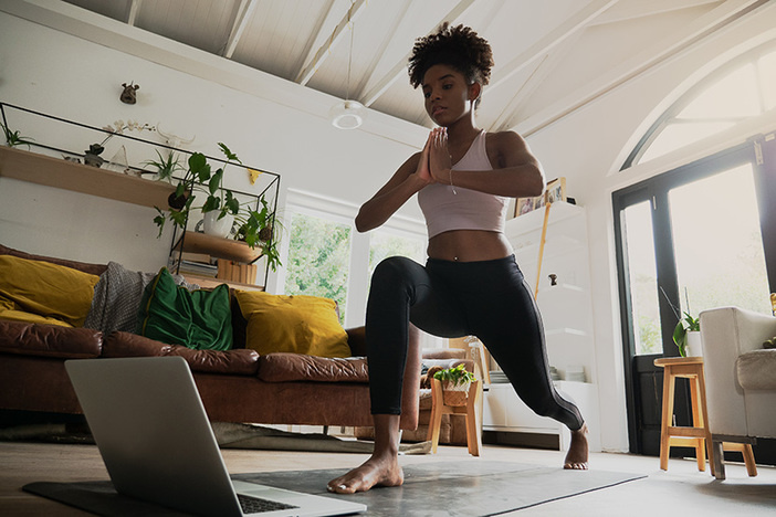 young mixed race female doing home workout or yoga from home, following an online workout on computer or online