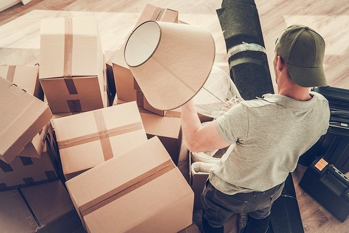 Caucasian Divorced Men in His 30s Moving Out From His Home. Staying Between Cardboard Boxes Preparing to Pack His Lamp.