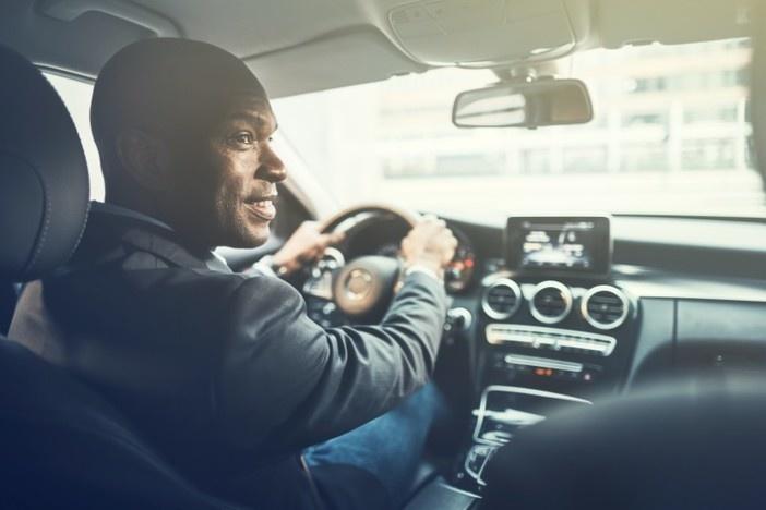 man driving luxury sedan looking out passenger window