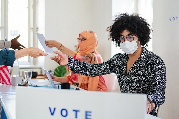 Group of people with face masks voting in polling place, usa elections and coronavirus.