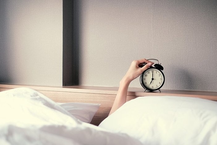 Woman sleep on the bed turns off the alarm clock wake up at the morning
