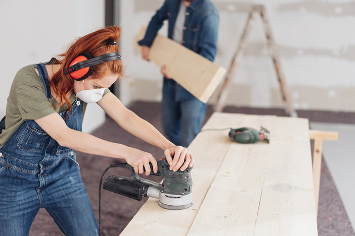young woman sanding planks of wood with an orbital sander in an unfinished room during DIY renovations