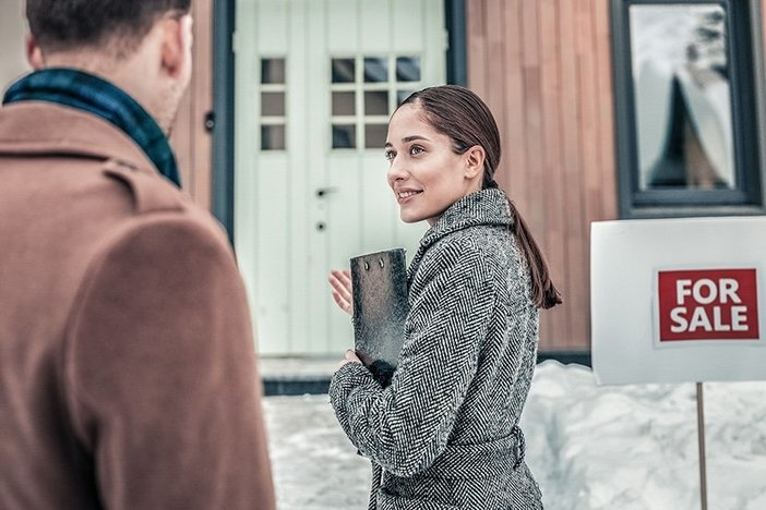 Smiling realtor greeting her customers outside the house for sale in winter with snow on ground