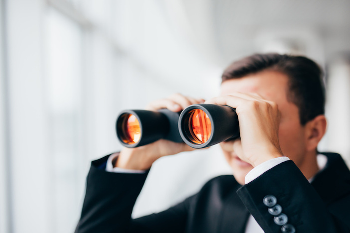 Handsome Business man looking with binoculars over panoramic windows