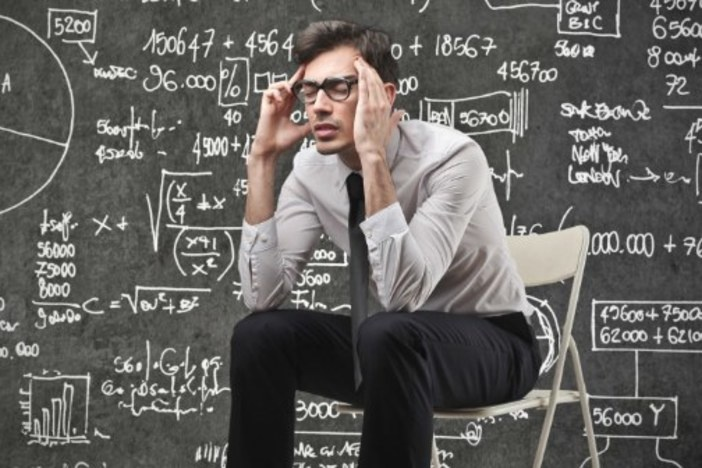 man sitting clutching temples in front of blackboard filled with calculations