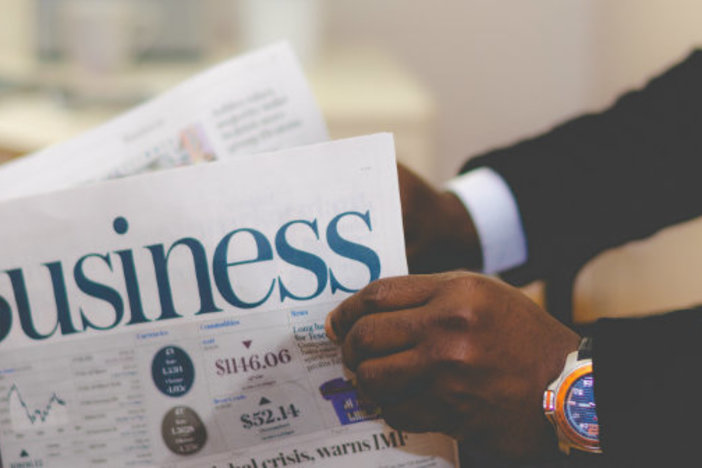 closeup of man in suit holding newspaper business section checking stock market