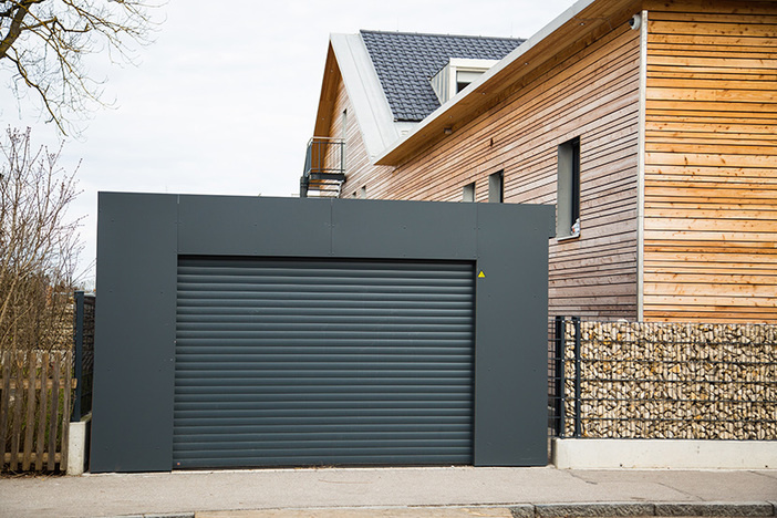 detached garage painted black with black garage door next to a modern looking house with natural wood siding exterior