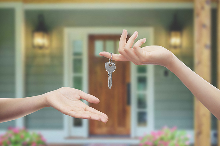 closeup of human hand with key dropping key into another person's open palm in front of a house