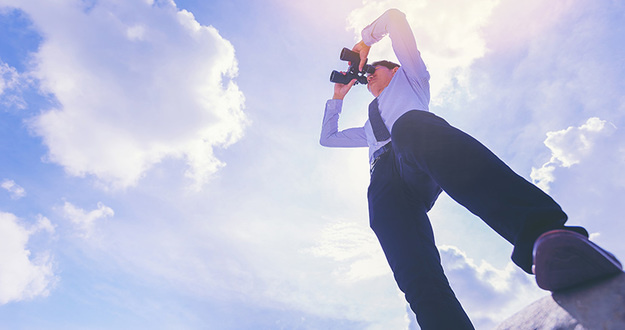 Businessman looking through binocular. searching for goal concept. low angle view.